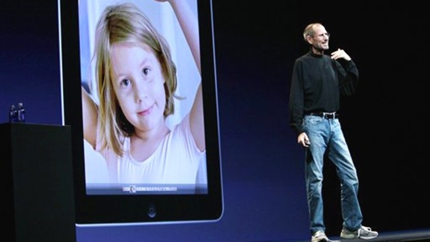 Apple CEO Steve Jobs, with the Apple iPad displayed over his shoulder, delivers the keynote address during the Apple Worldwide Developers Conference, Monday, June 7, 2010, in San Francisco.