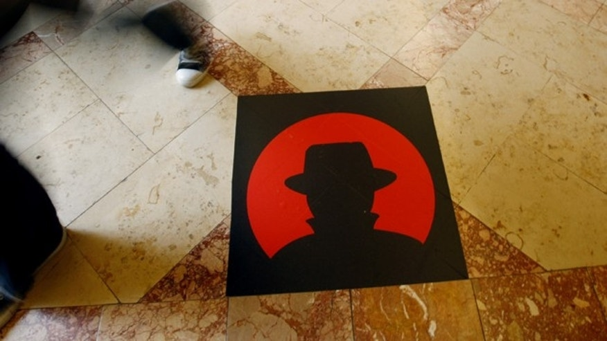 A man passes a logo of the Black Hat technology conference in Las Vegas on Wednesday, July 28, 2010.
