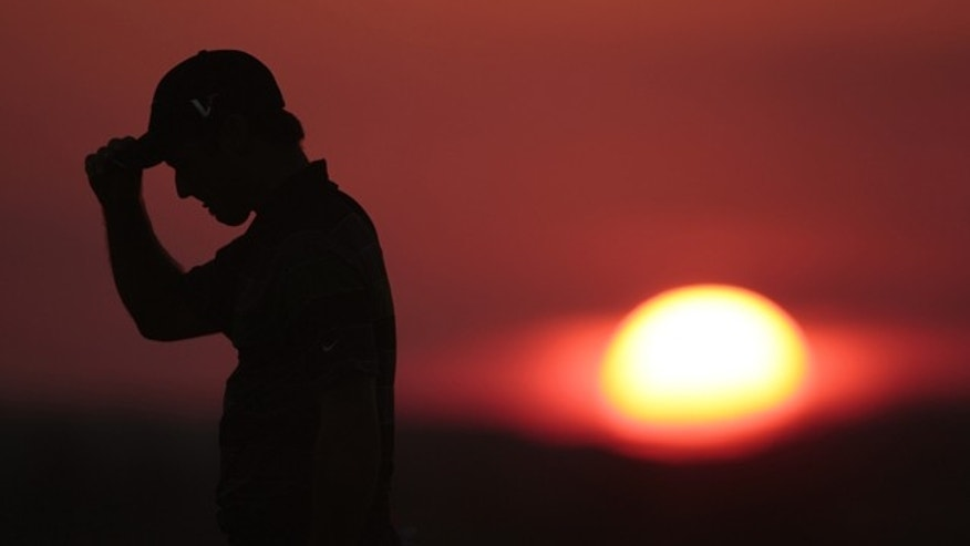 Trevor Immelman of South Africa walks off the 10th hole as the sun sets during the first round of the PGA Championship golf tournament Thursday, Aug. 12, 2010, at Whistling Straits in Haven, Wis. (AP Photo/Charlie Riedel)