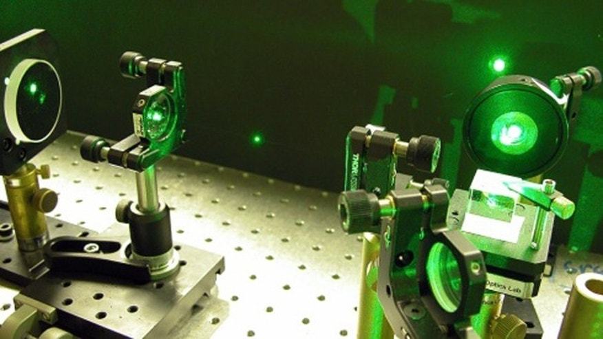 A tractor beam in action suspends a small particle over an optics table.