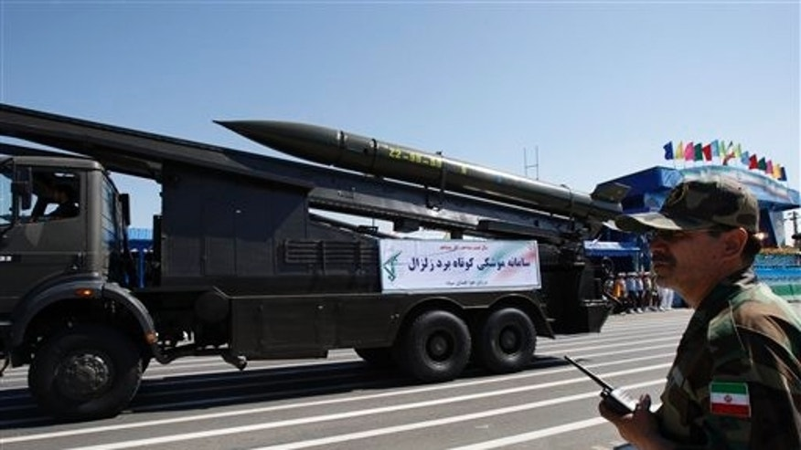A Zelzal, or earthquake, missile is displayed by the Iranian Revolutionary Guard, as a member of the Guard stands at right, during a military parade marking the 30th anniversary of outset of the 1980-88 Iran-Iraq war, in front of the mausoleum of the late revolutionary founder Ayatollah Khomeini, just outside Tehran, Iran, Wednesday, Sept. 22, 2010.