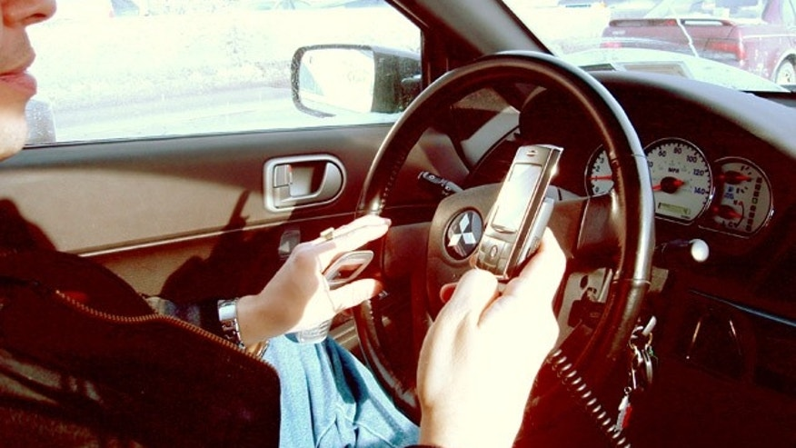 A driver in a Mitsubishi Galant uses a handheld mobile phone.