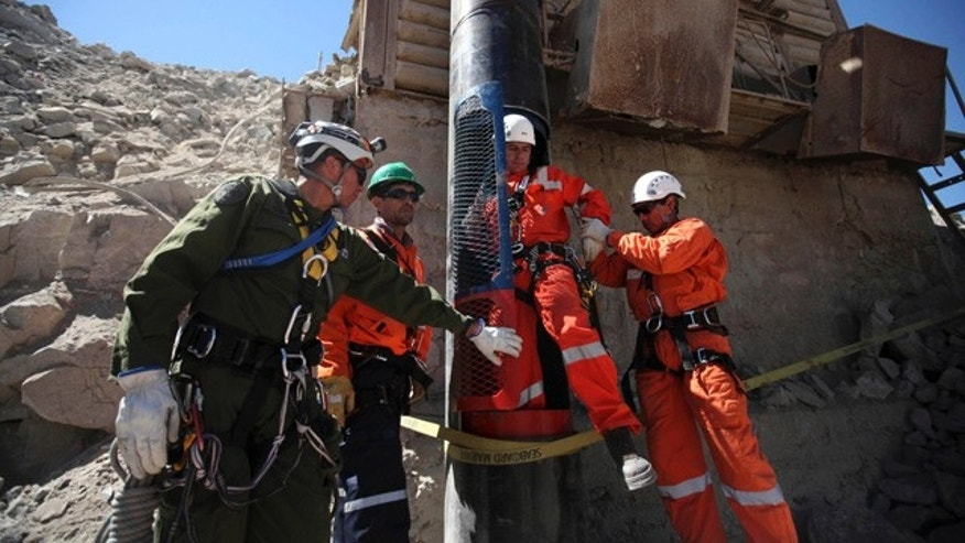 Rescue workers help as a colleague leaves a capsule after performing a dry run test for the eventual rescue of the 33 miners trapped at the San Jose mine, near Copiapo, Chile, Monday, Oct. 11, 2010.