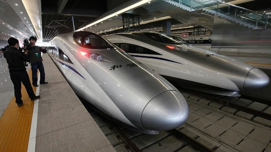 Journalists photograph the bullet trains of a new high-speed railway linking Shanghai with Hangzhou Tuesday, in Shanghai, China.