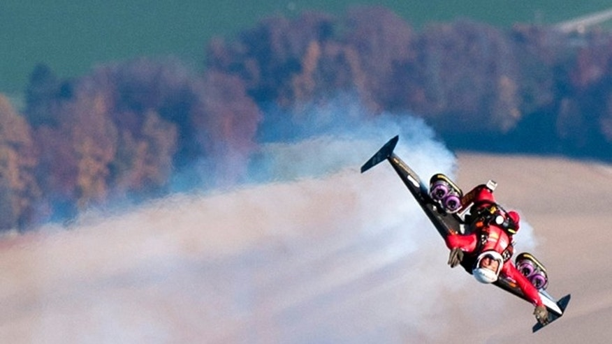 Swiss pilot Yves Rossy, the first man in the world to fly under a jet-fitted wing, speeds through the air to perform a looping in Bercher, western Switzerland, Friday, Nov 5, 2010.  Rossy has completed two aerial loops using his custom-made jet-propelled wingsuit. Rossy jumped from a hot-air balloon above Lake Geneva and performed the daredevil stunt before landing safely with a parachute.