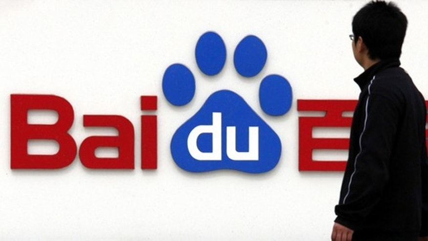 A pedestrian looks at the company logo of Baidu as he walks past company headquarters in Beijing March 24, 2010.