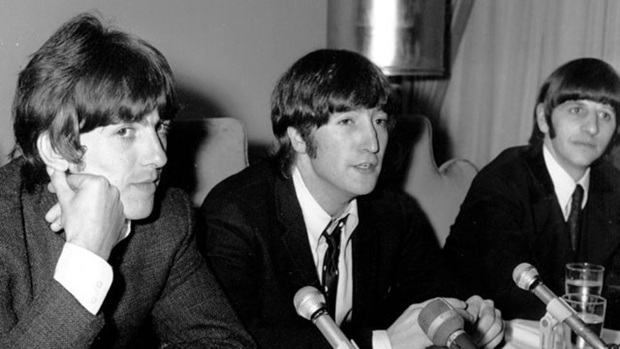 In this Aug. 11, 1966 file photo, John Lennon of the Beatles, center, is flanked by bandmates George Harrison, left, and Ringo Starr during a press conference.