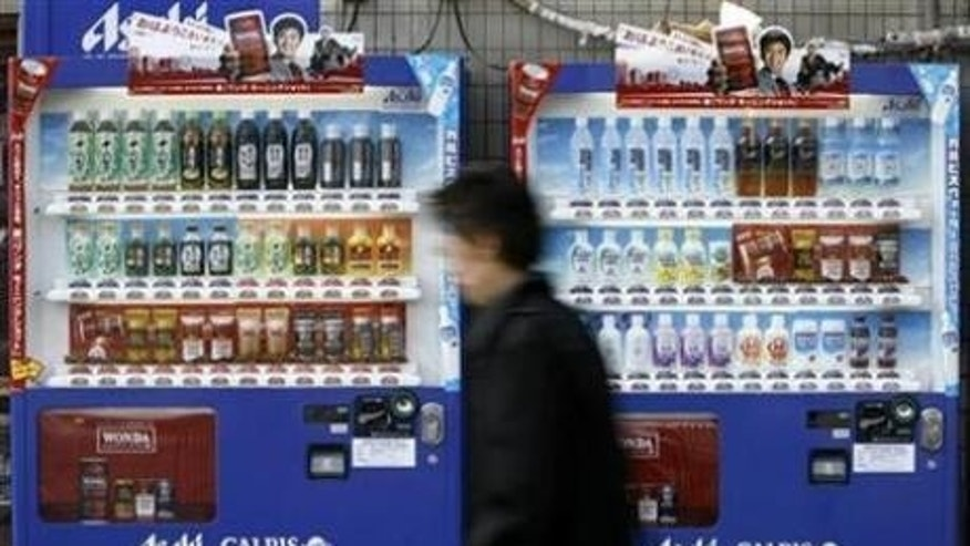 A man walks past vending machines of Asahi Soft Drinks in Tokyo in this December 1, 2008, file photo.
