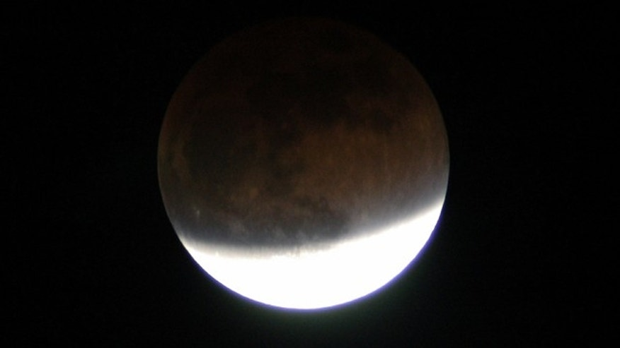 In this 2003 lunar eclipse viewed from Merritt Island, Fla., the full moon changes color because it is being lit slightly by sunlight passing through the Earth's atmosphere.