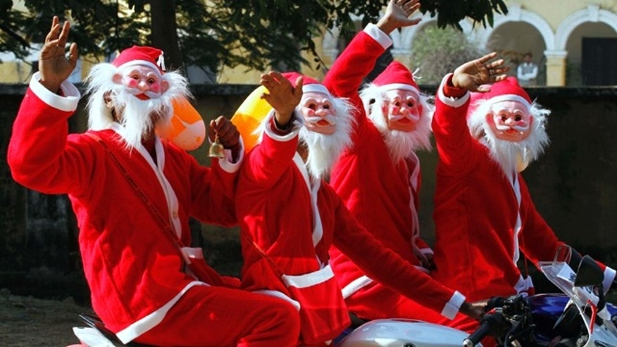 Indian men dressed as Santa Claus react to camera as they ride a motorcycle in Allahabad, India, Sunday, Dec. 19, 2010. (AP Photo/Rajesh Kumar Singh)