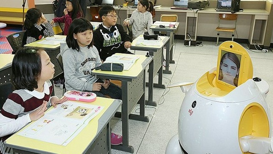 "English-teaching robot ""Engkey"" stands in front of children at an elementary school in Daegu, southeast of Seoul. 29 of the robots, about one meter high with a TV display panel for a face, wheeled around the classroom while speaking to the students, reading books to them and dancing to music by moving their head and arms."