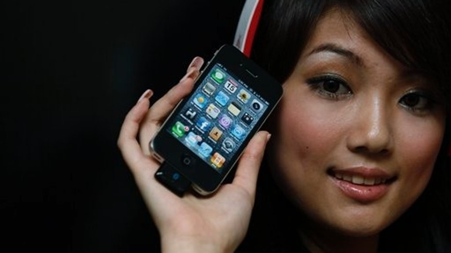 A model holds the latest iPhone 4 (with an attached Bluetooth device) during a promotional event in Hong Kong Thursday July 15, 2010.