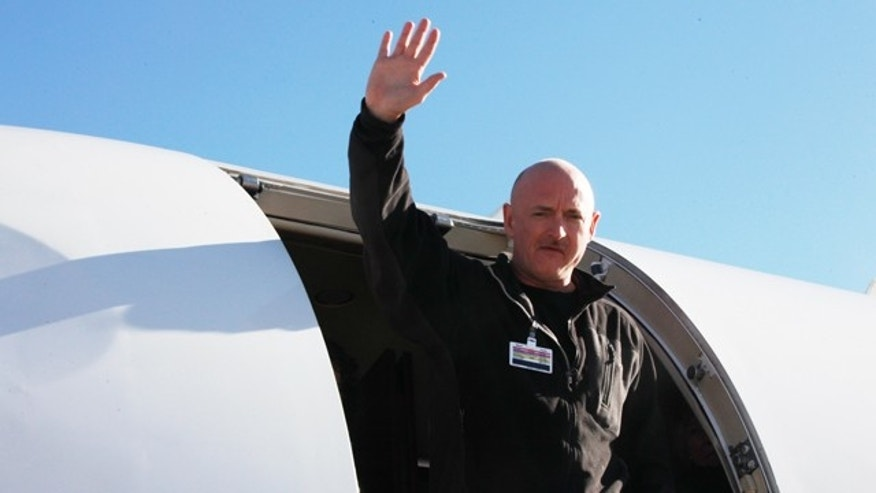Astronaut Mark Kelly waves after his Rep. Giffords was loaded onto an airplane in Tucson, Ariz., as she is transferred to a rehabilitation center in Houston, Friday, Jan. 21, 2011.