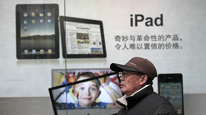 Jan. 26: A man stands near Apple's iPad advertisement in Shanghai, China.
