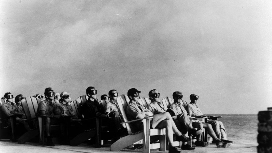 Operation Greenhouse, 1951 High ranking military personnel sit in rows of deck chairs, wearing goggles, while illuminated by the flare of an atomic detonation at the Atomic Energy Commission's Pacific Proving Ground during Operation Greenhouse, 1951.