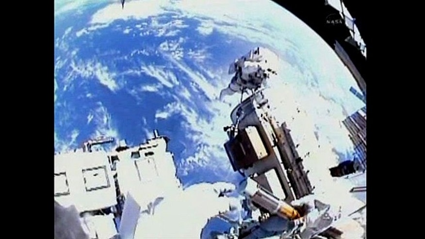 "The view from spacewalker Alvin Drew's helmet cam shows him opening the ""Message in a Bottle"" to capture space."