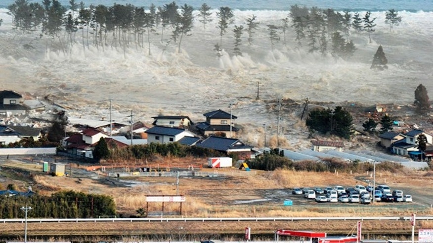 March 11: Waves of tsunami hit residences after a powerful earthquake in Natori, Miyagi prefecture.