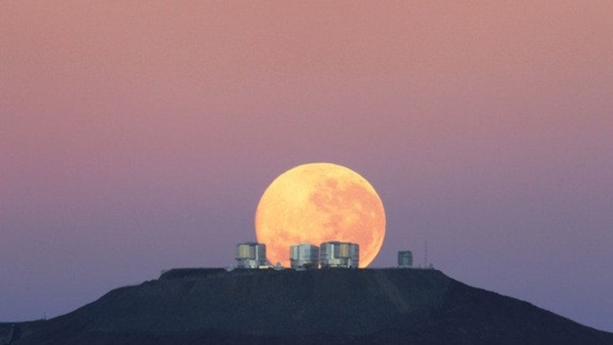 The dazzling full moon sets behind the Very Large Telescope in Chile's Atacama Desert in this photo released June 7, 2010 by the European Southern Observatory. The moon appears larger than normal due to an optical illusion of perspective.