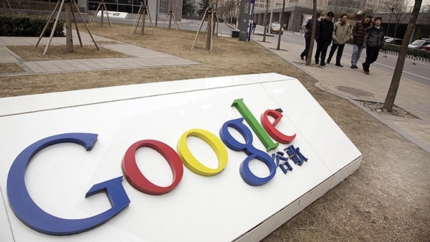 In a Monday March 22, 2010, file photo men walk past the Google China headquarters in Beijing, China.