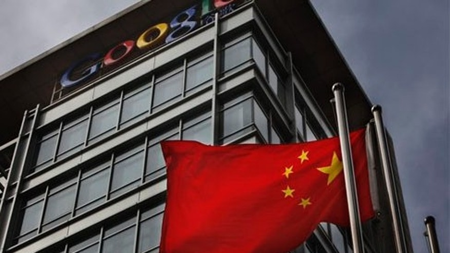 A Chinese flag blows in the air below the Google logo outside the Google China headquarters in Beijing on March 25, 2010.