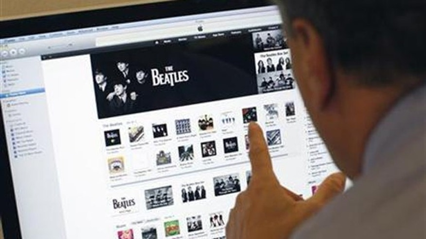A man poses as he looks at music from the legendary band The Beatles on Apple's itunes music store website seen on an imac computer in New York, November 16, 2010.