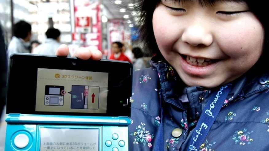 Feb. 26, 2011: Natsumi Miyasaka, 9, shows off Nintendo's newest computer game console, the Nintendo 3DS, at retail store Bic Camera in central Tokyo.