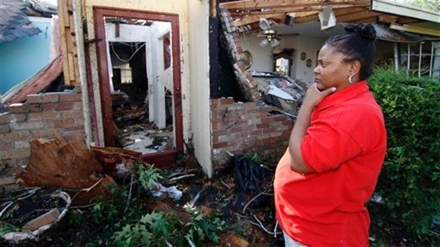 Frenchie Russell overlooks the remains of her tornado damaged home in Clinton, Miss., Friday, April 15, 2011. Russell and her husband were home when the tornado hit this morning and destroyed the house as well as others in her neighborhood. The state was hit by a line of severe storms that spawned at least one tornado causing extensive damage and multiple injuries. (AP Photo/Rogelio V. Solis)