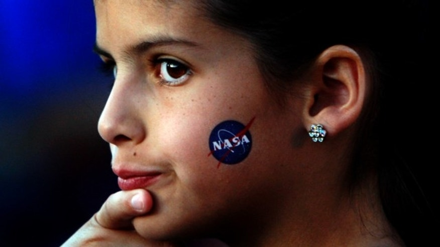 May 22, 2011: Fourth grader Alexandra Doe has a NASA symbol on her cheek as she waits to be called inside as Mesa Verde Elementary School students talk with Shuttle Endeavour astronauts.