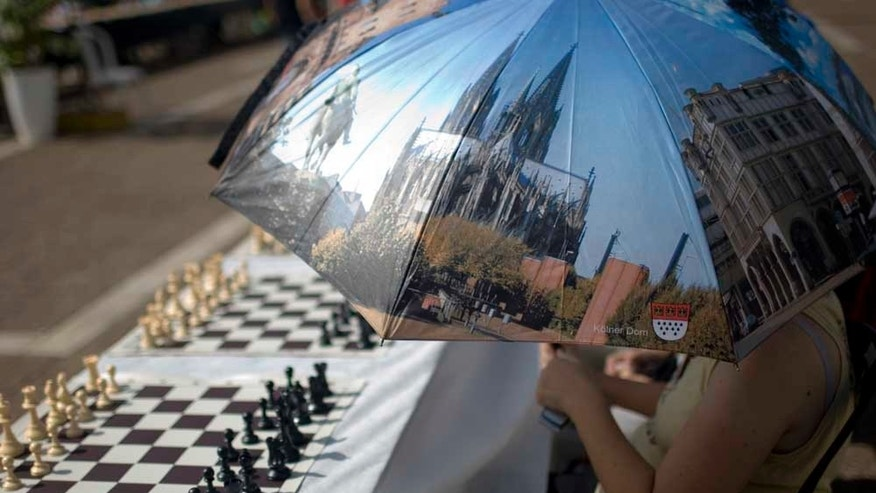 Oct. 21, 2010: A chess player holds a reflective parasol to protect herself from the sun as she waits to play against Israeli chess Grandmaster Alik Gershon, not pictured, during an attempt to break the Guinness world record of simultaneous chess play in Rabin square in Tel Aviv, Israel.