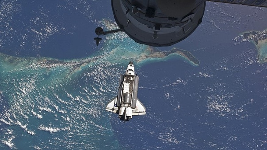 July 10: Space shuttle Atlantis hangs over the Bahamas prior to a perfect docking with the International Space Station. Part of a Russian Progress spacecraft which is docked to the station is in the foreground.