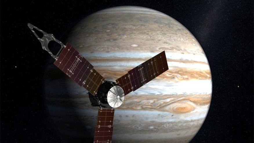 The Juno spacecraft passes in front of Jupiter in this artist's depiction.