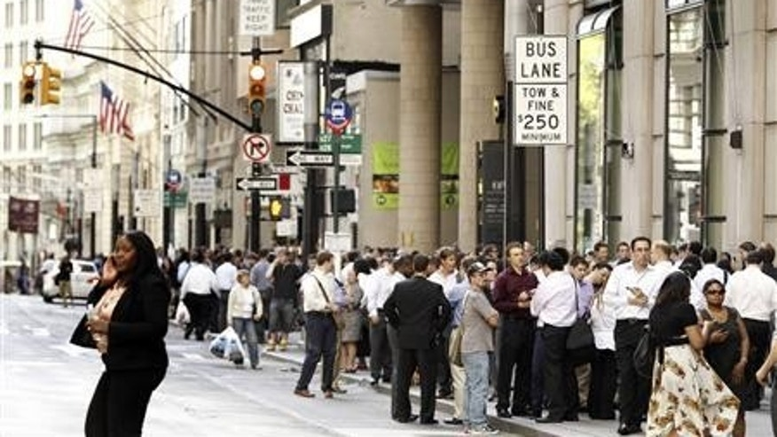 Office workers evacuated from buildings on Broadway in New York stand outside after a magnitude 5.9 earthquake that struck the US East Coast August 23, 2011.