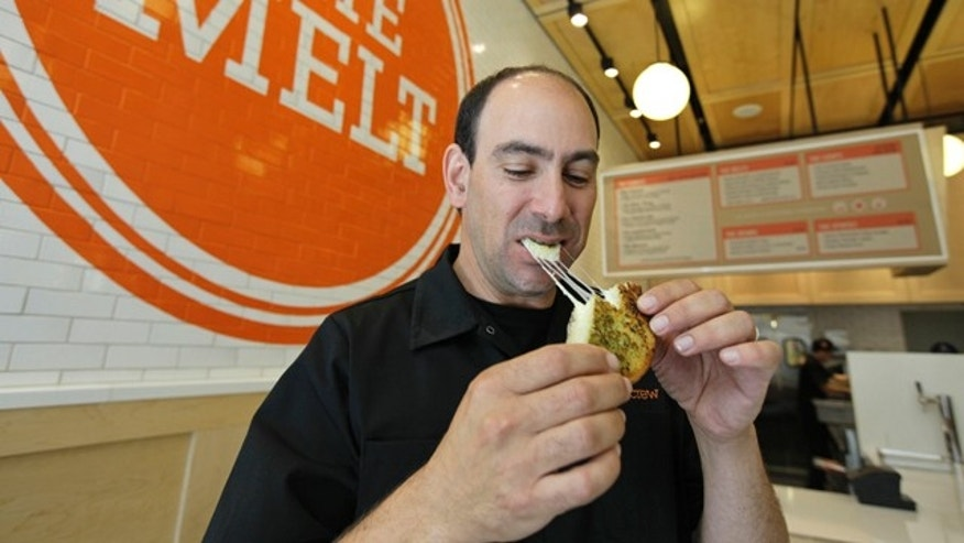 Aug. 25, 2011: Jonathan Kaplan bites into a melt called the Italian Job made with fontina and provolone cheese on garlic bread at The Melt in San Francisco. First, Flip Video camcorder creator Kaplan made it easy for consumers to shoot cheesy home movies. Now, hes hoping to popularize something cheesier and gooier by starting a grilled cheese restaurant business that combines fast food with high tech.