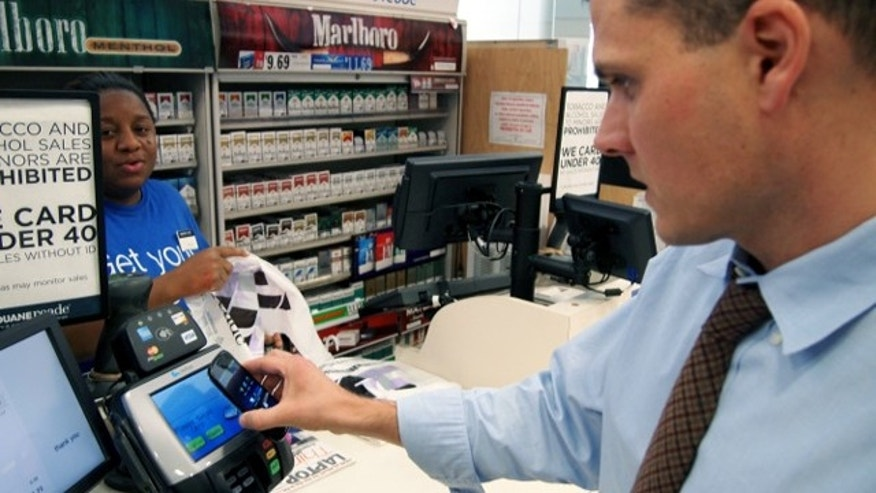 Laptop Magazine editor in chief Mark Spoonauer uses Google Wallet installed on a smartphone to make a purchase at a Duane Reade drugstore in New York City.