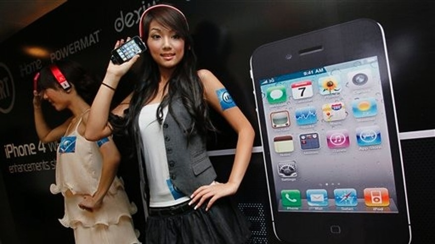 July 15, 2010: Models hold the iPhone 4 during a promotional event in Hong Kong.
