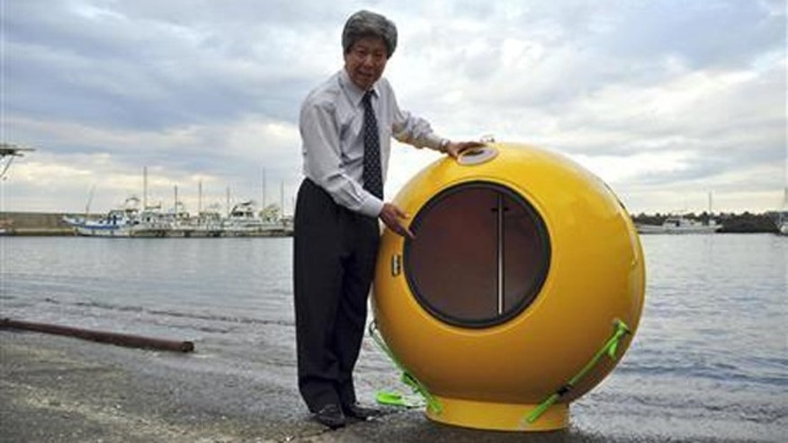 Cosmo Power President Shoji Tanaka speaks as he stands next to the company's personal flotation device ''Noah',' which could survive both an earthquake and the tsunami that might follow.