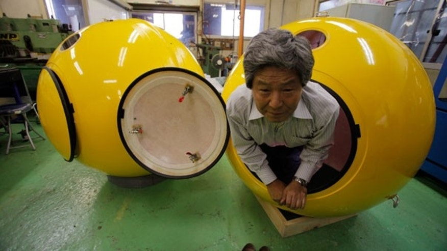 "Sept. 30: Cosmo Power Co. President Shoji Tanaka crawls out from a spherical earthquake and tsunami shelter ""Noah"" made of fiber enforced plastic at the company's factory in Hiratsuka, west of Tokyo."