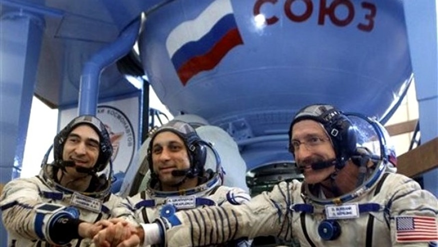 Sept. 2, 2011: U.S. astronaut Dan Burbank, right, with Russian cosmonauts Anton Shkaplerov, center, and Anatoly Ivanishin pose before their final preflight practical examination in a mock-up of a Soyuz TMA space craft at Russian Space Training Center in Star City outside Moscow, Russia.
