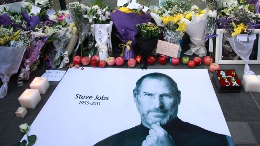Oct. 6, 2011: Fresh apples, flowers and a large poster of Steve Jobs are placed outside an Apple retail store in Beijing, China.