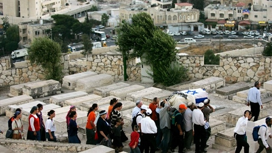 Israeli men carry a coffin wrapped in an Israeli flag and a prayer shawl as women follow during a reburial ceremony for fifteen Jewish settlers at the Mt. of Olives cemetery in Jerusalem. A Jewish group is using 21st-century technology to map every tombstone in the ancient cemetery on the Mount of Olives, a sprawling, politically sensitive necropolis of 150,000 graves stretching back three millennia.
