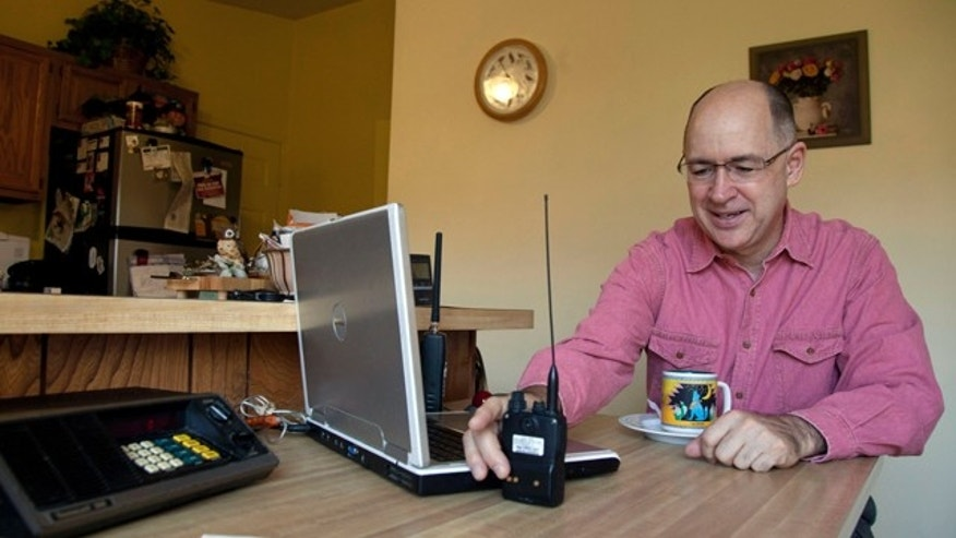 Nov. 19, 2011: Scanner hobbyist Rick Hansen holds his scanner/Ham radio device at his home in Silver Spring, Md.