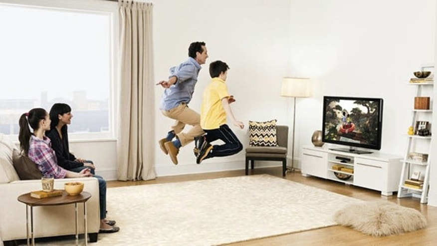 A family plays a video game on the Xbox 360, thanks to the motion-sensing Kinect controller.