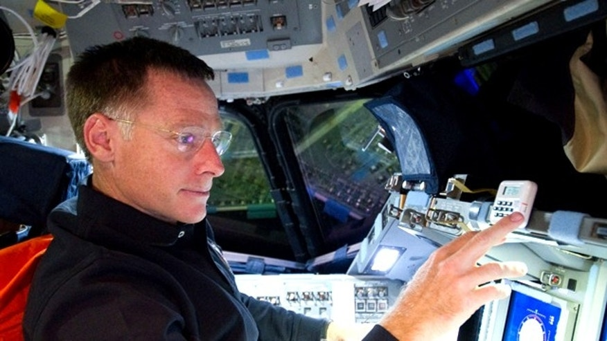Astronaut Chris Ferguson, STS-135 commander, is pictured at the commander's station on the forward flight deck of the space shuttle Atlantis during the STS-135 mission's third day in space.