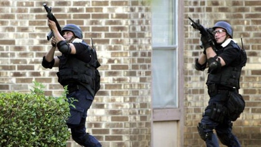 Members of a SWAT unit take aim at a second floor apartment window during a 2006 standoff in which a shooter wounded three police officers and a state trooper.