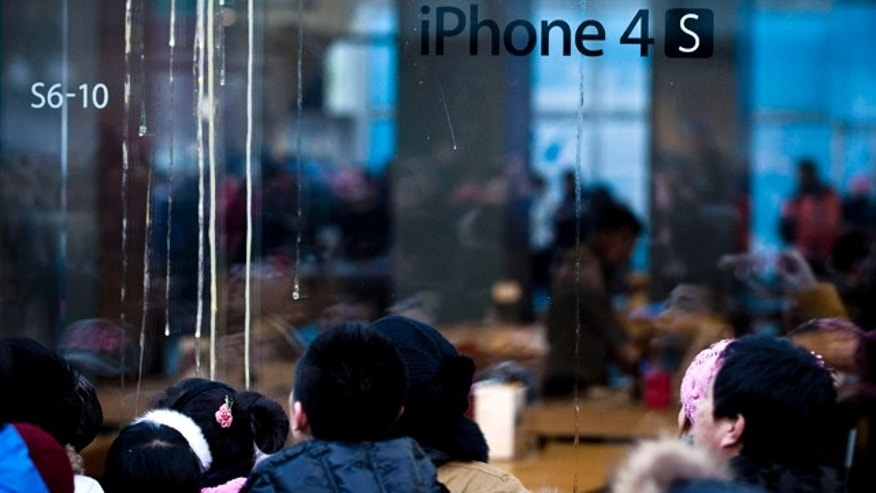 Jan. 13, 2012: Chinese people look at the egg's stains, left, on the Apple store's glass wall as they wait for the store to open to sell the iPhone 4S model in Beijing.