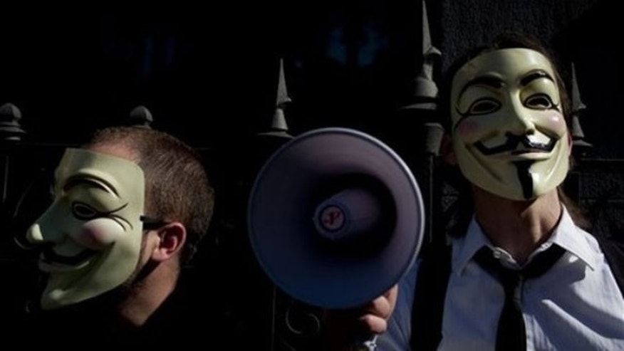 "In this May 15, 2011 file photo people wearing masks often used by a group that calls itself ""Anonymous"" take part in a rally in Madrid."