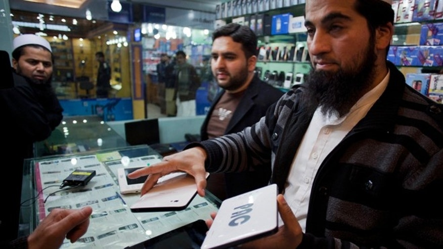 Feb. 8, 2012: Mohammad Imran holds Pakistani-made PACPad computer tablets at his electronics store in Rawalpindi, Pakistan. Pakistani military engineers who make high-tech air force instruments are being put to work on the device, which is built from Chinese-made components and runs on Google's Android system. The Pakistan Aeronautical Complex (PAC) also makes an e-reader and small laptop.