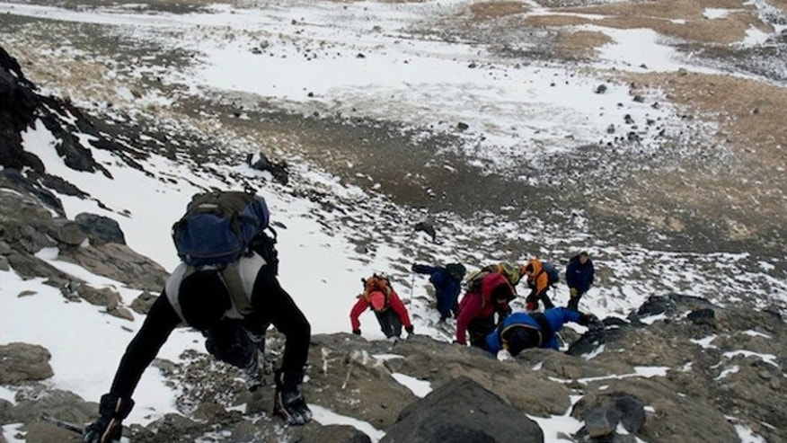 Visitors climb a rocky slope in Antarctica. Tourists and scientists are unknowingly bringing with them invading species that can disrupt the continent's pristine environment.