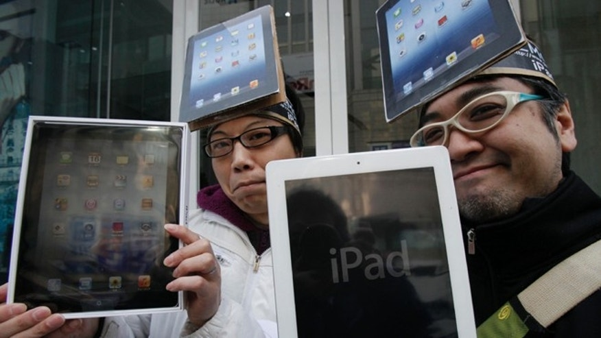 March 16, 2012: Japanese Ryota Musha, 41, right, and Hisanori Kogure, 31, show off new iPad tablet computers they purchased, in Tokyo. Sales of the third version of Apple's iPad began Friday morning in Japan.