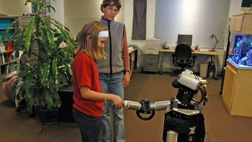 A child interacting with Robovie, a remotely controlled humanoid robot. In the near future, children may view such robots as friends.
